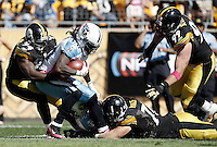 PITTSBURGH, PA - OCTOBER 09:  Lawrence Timmons #94 and Chris Hoke #76 of the Pittsburgh Steelers tackle Chris Johnson #28 of the Tennessee Titans during the game on October 9, 2011 at Heinz Field in Pittsburgh, Pennsylvania.  (Photo by Jared Wickerham/Getty Images)