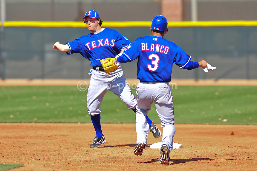 Feb 24, 2011; Surprise, AZ, USA; Texas Rangers second baseman Ian Kinsler turns a double play in front of shortstop Andres Blanco during an intra-squad game played by the Rangers at the Surprise Recreation Campus.