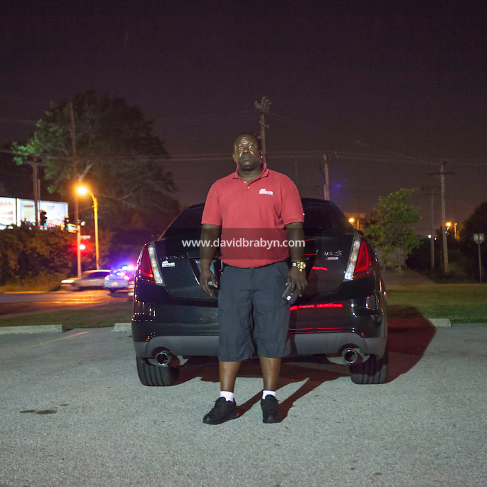 HSUL 20140818 United States, Ferguson, MO. <br /> Vic Hayes poses for the photographer on West Florissant Avenue in Ferguson, Missouri, early on August 19, 2014, as he waits for police officers to let him return home after some violence marred protests against the shooting death of Michael Brown. Photographer: David Brabyn