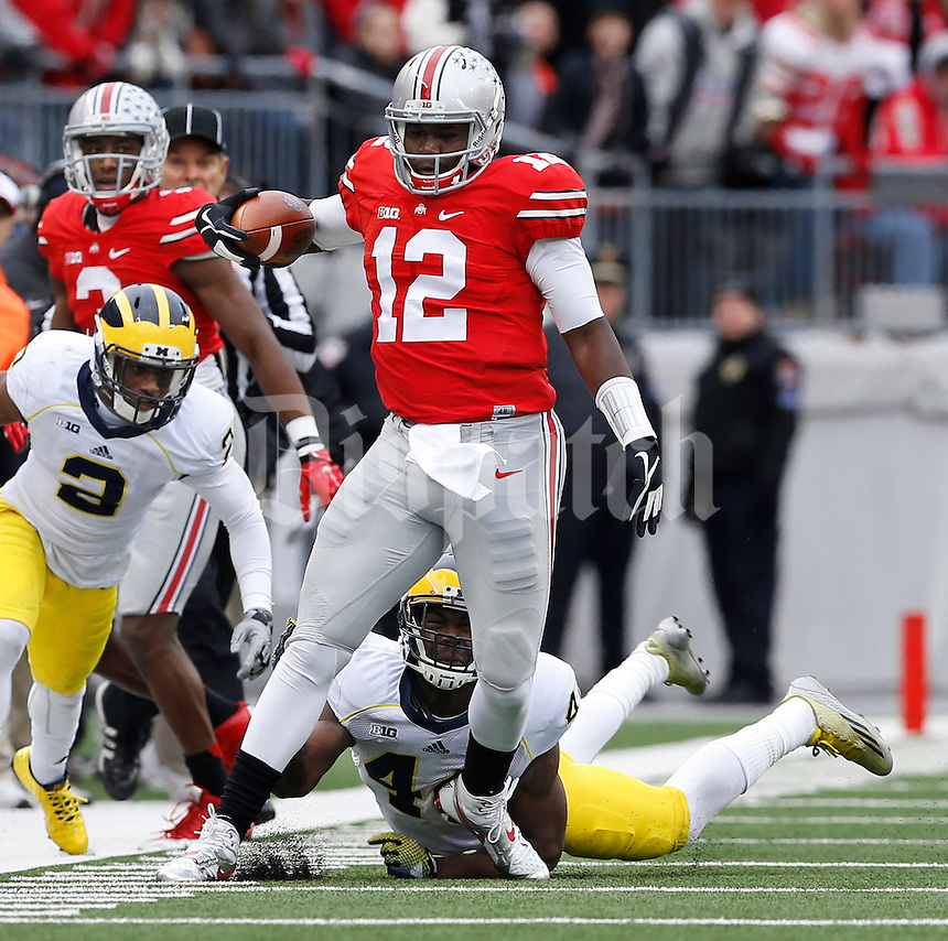 Ohio State Buckeyes quarterback Cardale Jones (12) eludes Michigan Wolverines defensive back Delano Hill (44) and defensive back Blake Countess (2) during the fourth quarter of the NCAA football game at Ohio Stadium on Nov. 29, 2014. Jones took the field after starter JT Barrett left with a broken ankle. (Adam Cairns / The Columbus Dispatch)
