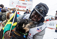 Newton Marshall poses with his lead dog in the finish chute after arriving in 43rd place in Nome on Friday March 14 during the 2014 Iditarod Sled Dog Race.<br /> <br /> PHOTO (c) BY JEFF SCHULTZ/IditarodPhotos.com -- REPRODUCTION PROHIBITED WITHOUT PERMISSION