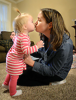 SELLERSVILLE, PA -  MARCH 7:  Emma Davies (L), 1 year old, kisses her mother Lisa Davies (R) March 7, 2014 in Sellersville, Pennsylvania. Emma Davies is suffering from a rare hematological disease. She will be getting a bone marrow transplant from her older sister. With bills stacking up, a friend of the Davies family has set up an online fundraiser to help.(Photo by William Thomas Cain/Cain Images)