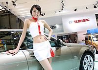shanghai, china - april 20: a model poses for photographs on a car during shanghai motor show on april 20, 2009 in shanghai, china. shanghai auto show opened monday for the press and will be open april 24-28 for the public. china is the only major auto market still growing despite the global economic slowdown. u.s. and global auto makers see china as the place where they can find the sales they desperately lack in their home market. chinese automakers see the opportunity to assess themselves as major players in the world market. (photo by lucas schifres/getty images)