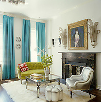 Vintage sconces flank the marble fireplace in the master bedroom with a pair of Fornasetti plates arranged between turquoise curtains chosen to create a vivid contrast to the bright olive green of an adjacent antique loveseat