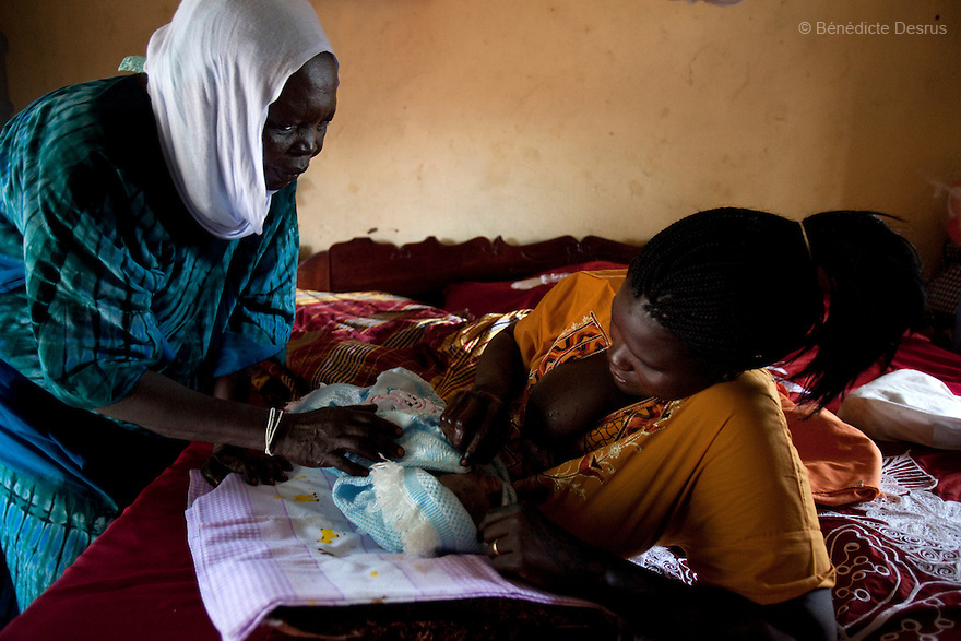 2011 - Juba, Republic of South Sudan - Lushi Rashid (R), a 29 year old muslim South Sudanese woman, breast feeds her new born baby boy at her family home with the help of Regabia Ahmad (L), a qualified birth attendant, in Juba, the capital city of South Sudan. Regabia has been delivering babies in South Sudan for over twenty years. she was trained by the health ministry and works at a local primary health clinic. With fewer than 100 trained midwives for a population of over eight million, South Sudan has the highest maternal mortality rate in the world.  One in seven South Sudanese women is likely to die because of complications from delivery. Just 10 per cent of South Sudanese women have access to medical professionals during childbirth. Photo credit: Benedicte Desrus