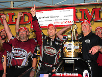 Nov 14, 2010; Pomona, CA, USA; NHRA top fuel dragster driver Larry Dixon (center) celebrates with crew chief Jason McCulloch (left) and team owner Alan Johnson after winning the 2010 top fuel championship during the Auto Club Finals at Auto Club Raceway at Pomona. Mandatory Credit: Mark J. Rebilas-