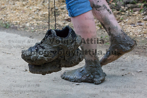 Woman walks with muddy shoes and feet after wetcihng the swarming of the long-tailed mayfly (Palingenia longicauda) on the river Tisza in Tiszainoka (some 135 km south-east from Budapest), Hungary on June 23, 2013. ATTILA VOLGYI<br /> The long-tailed mayfly larves live 3 years under water level in the river banks then swarm out for a one day period of their life to die after mating.