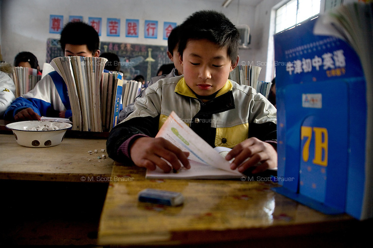 Children study in a classroom in Yibei Middle School in Yibei Township, Guanyun County, Jiangsu Province, China.  The Pfrang Association, a German charity based in Nanjing, China, sponsors a number of children in the school, providing money for boarding, food, clothing, school supplies, and other necessities to continue schooling.  The majority of children at this school come from poor farming families in rural Jiangsu Province, China.