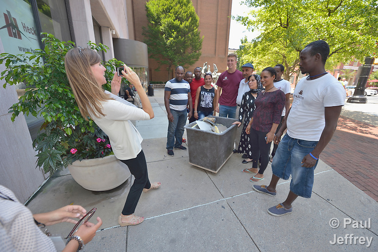 Penny Gushiken (left) takes a photo of her cultural orientation class for newly arrived refugees in downtown Lancaster, Pennsylvania. The class was engaged in a scavenger hunt of sorts, tasked with finding people engaged in specific activities such as listening to music, talking on the phone, and eating. In this case, the class was supposed to find someone taking out the trash. They found a man pushing a cart of trash out of an office building, and Gushiken took a photo of the group posing with him. The class is sponsored by Church World Service. <br /> <br /> Photo by Paul Jeffrey for Church World Service.