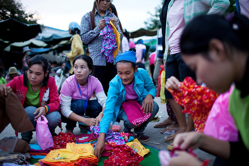 Workers from the Shen Zhou garment factory shop for clothes at a small open-air market just outside the factory in Phnom Penh, Cambodia, September 14, 2011. A pair of shorts usually costs about 75 cents to US$1.
