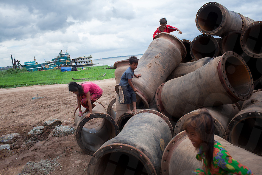 May 27, 2012 - Phnom Penh, Cambodia. Children play on pipes near a sand dredging site on the confluence of the Mekong and Tonle Sap rivers. © Nicolas Axelrod / Ruom