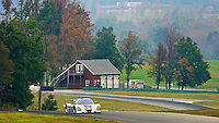 A prototype race car races past a barn and trees at Virginia International Raceway, Alton, VA. (Photo by Brian Cleary/www.bcpix.com)