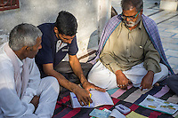 Technoserve's Field Extension Officer, Surender Singh, sits together with a group of guar farmers as they have a committee meeting in Bamanwali village, Bikaner, Rajasthan, India on October 24th, 2016. Non-profit organisation Technoserve works with farmers in Bikaner, providing technical support and training, causing increased yield from implementation of good agricultural practices as well as a switch to using better grains better suited to the given climate. Photograph by Suzanne Lee for Technoserve