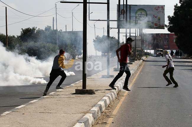 Palestinian protesters run for cover from a tear gas canister fired by Israeli troops during clashes following a protest in solidarity with Palestinian prisoners held in Israeli jails, at the Hawara checkpoint near the West Bank city of Nablus on Aug. 18, 2016. Photo by Nedal Eshtayah