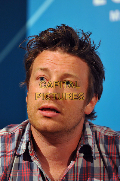 An Audience with Jamie Oliver press conference.  British TV chef and food campaigner discusses a range of international food issues, ranging from diet-related disease to sustainability, to mark the London 2012 Olympics. London Media Centre, London, England..August 6th, 2012.headshot portrait white blue red check shirt stubble facial hair mouth open.CAP/BF.©Bob Fidgeon/Capital Pictures.