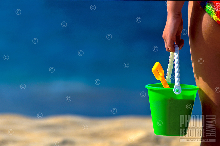 Young girl holds beach bucket at Big Beach, Makena, Maui.