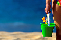 Young girl holds beach bucket at Big Beach, Makena, Maui.