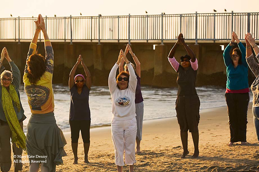 Senior mixed ethnic females follow exercises with leader on the beach at sunset in Playa Del Rey, CA.
