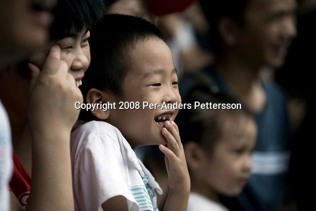 GUANGZHOU, CHINA OCTOBER 3: A boy laughs as he watches an animal show with monkeys at Chimelong Paradise Theme Park on October 3, 2008 outside Guangzhou, China. Millions of Chinese took a weeklong break during the National Holiday and one of the Golden weeks during the year. Chimelong is one of the best and most popular amusement parks in China with attractions such as a driving safari, animal shows and the biggest rollercoaster in the world with 10 loops. Chinese people love theme parks and new ones are opening constantly. It's estimated that there's about 2400 theme parks in the country. (Photo by Per-Anders Pettersson) ..