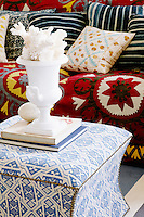 The living room is furnished with an eclectic mix of fabrics, pattern and colour