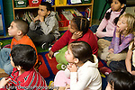 Education Elementary Grade 2 class sitting on floor listening as volunteer (not seen) reads to group  horizontal