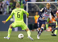 CF Monterrey forward Humberto Suazo passes the ball in front of Seattle Sounders FC defender Osvaldo Alonso during a CONCACAF Champions League match at CenturyLink Field in Seattle Tuesday Oct. 18, 2011. CF Monterrey won the game 2-1.