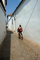 View of woman riding a bike through a cobbled alley in the Juderia Quarter, Cordoba, Andalusia, Spain.
