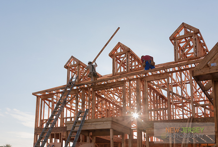 New Residential House Construction with wood framing and roof trusses and dormers against a blue sky.  Intentional lens flare.