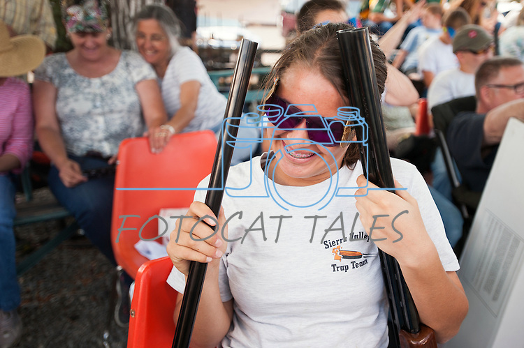 Madison Hood, 14, from the Sierra Valley Trap Club, laughs while holding two guns during the California Youth Shotgun Shooting Association&rsquo;s championship shootout at the Capitol City Gun Club in Carson City, Nev. on Saturday, May 2, 2015.<br /> Photo by Kevin Clifford/Nevada Photo Source