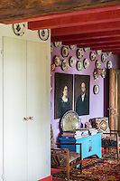 This adjacent sitting room has a purple signature wall featuring a colourful plate display