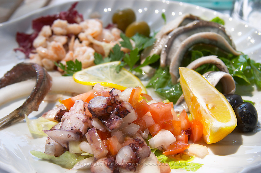 Salad with calamares calamari, octopus, ink fish and vegetables. Other seafood in the background. Hotel and restaurant Kompas. Uvala Sumartin bay between Babin Kuk and Lapad peninsulas. Dubrovnik, new city. Dalmatian Coast, Croatia, Europe.