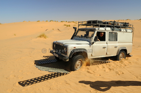Africa, Mauritania, Sahara Desert, between Choum and Atar. Recovering a stuck tourists Land Rover Defender TD5 Station Wagon by using sand channels out of the Sahara sand while crossing some dunes. --- RELEASES AVAILABLE! Automotive trademarks are the property of the trademark holder, authorization may be needed for some uses.