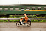 VIETNAM, Hanoi, Countryside, a man passes a train on his moped in the rain