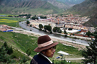 A Tibetan pilgrim looks out over the Labrang Monastery in Xiahe, Gansu, China. Xiahe, home of the Labrang Monastery, is an important site for Tibetan Buddhists.  The population of the town is divided between ethnic Tibetans, Muslims, and Han Chinese.