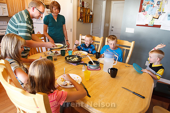 Trent Nelson  |  The Salt Lake Tribune.The Burton family gathers for dinner Thursday, August 25, 2011. The Burton family are trying to sell their home in Tooele, Utah, due to a job transfer. Despite adding more than $20,000 in improvements since they purchased their home in 2005, they are now asking only what they paid for the home. Standing are Scott and Angela Burton. Seated left to right are Emily, Kaitlyn, Spencer, Jeffrey and Zachary Burton