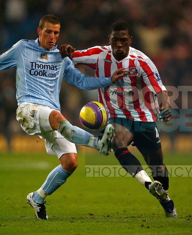 Manchester City's Elano tussles with Sunderland's Dickson Etuhu
