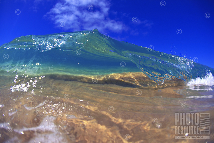 Beautiful small wave cresting at the shore break of Makena beach on the island of Maui, Hawaii.