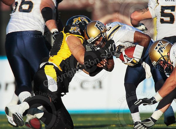 Aug 3, 2007; Hamilton, ON, CAN; Winnipeg Blue Bombers quarterback (5) Kevin Glenn is sacked by Hamilton Tiger-Cats defensive lineman (9) Nautyn McKay-Loescher during the first quarter at Ivor Wynne Stadium. Mandatory Credit: Ron Scheffler