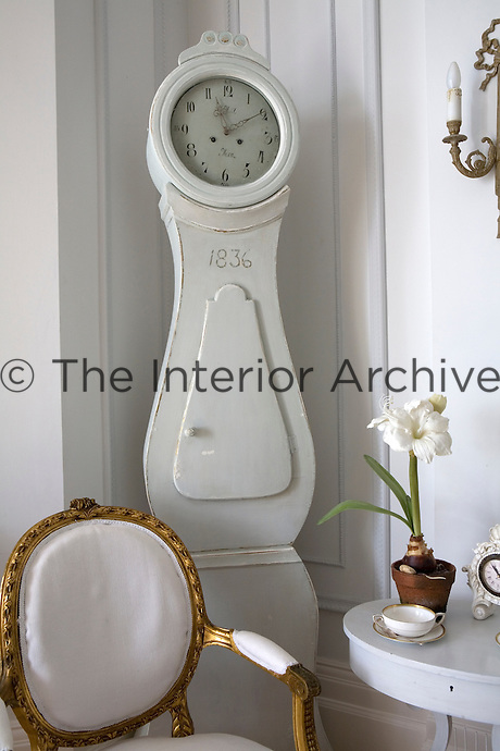 A gilded Gustavian carver chair, side table and a Mora clock in the corner of the living room