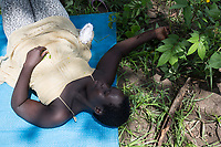 Uganda - Adjumani - Mary, a South Sudanese orphan, lies in the grass.<br /> Created in 1994, the orphanage is managed by South Sudanese International Widows Association to Save Orphans and moved in February 2017 from the South Sudanese city of Kajo-Keji to Uganda because of security reasons. It currently hosts 55 children in the city of Adjumani and an additional 27 in Palorinya refugee camp.