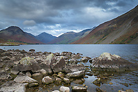 Rocks and boulders on shore of lake and mountains L to R Yewbarrow, Great Gable (centre), Lingmell, and The Screes by Wast Water in the Lake District, Cumbria, UK