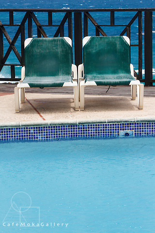 Tourism Barbados - Two sunbeds by a turquoise pool with Caribbean style fence and blue sea in the background