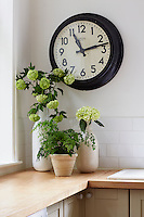 A retro clock by Smith + Co hangs above cut hydrangeas.