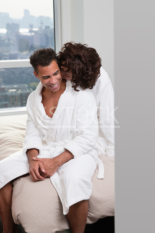 USA, New York City, couple sitting on bed, woman kissing man