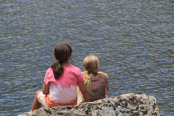 Two girls sitting at lake, Boulder, Colorado, USA .  John leads private photo tours in Boulder and throughout Colorado. Year-round.