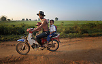 Children get a ride to school on a motorcycle in the village of Chek Angkor in northern Cambodia.