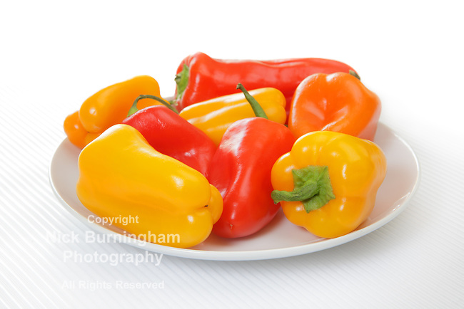 Multi-colored mini bell peppers on white plate on light textured background.  Fades to white on top edge.