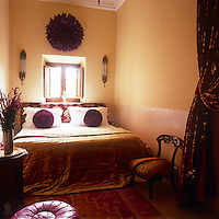 A guest bedroom decorated in tones of gold and purple. A double bed is placed below a small window.