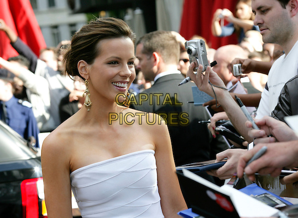 """KATE BECKINSALE.Leaving the UK premiere of """"Die Hard 4.0: Live Free or Die Hard"""" at the Empire Leicester Square, London, England..June 20th, 2007.half length fans crowd dangling gold earrings strapless white dress .CAP/CAM.©Andre Camara/Capital Pictures"""