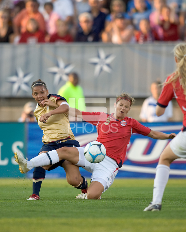 Natasha Kai (United States, gold) passes through defender, Siri Nordby (Norway, red). The United States defeated Norway, 1-0, in Rentschler Stadium, July 14, 2007.